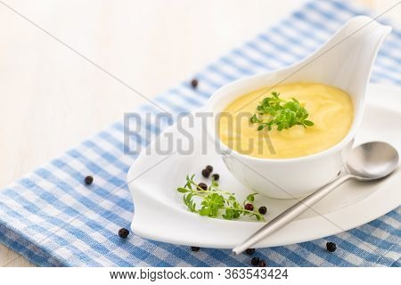 Hollandaise Sauce. Classic French Cuisine Sauce. Emulsion Sauce Of Butter And Egg Yolks With Vinegar