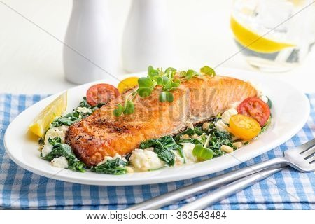Roasted Salmon Fillet With Spinach And Cheese Garnish With Cherry Tomatoes And Lemon. A Large Portio