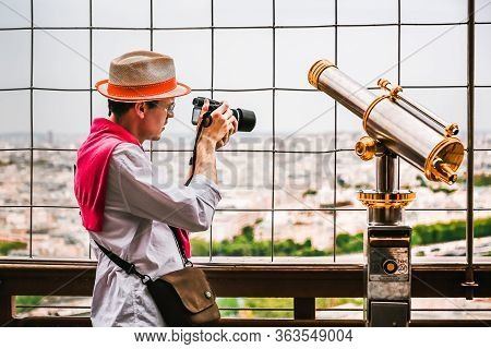Paris, France - April 22, 2019: Man Tourist Taking Picture Of French City Skyline. Vintage Coin Oper