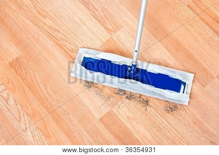 Image of a modern floor dusting mop being used to clean hair and dirt on a wooden laminate floor.