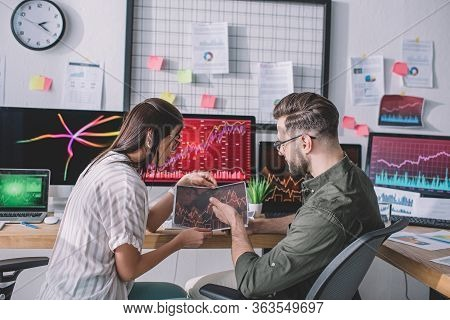 Side View Of Information Security Analysts Using Charts While Testing Security Of Computer Systems