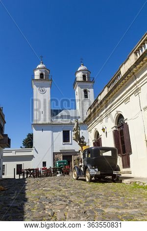 Obsolete Cars, In Front Of The Church Of Colonia Del Sacramento, Uruguay. It Is One Of The Oldest Ci