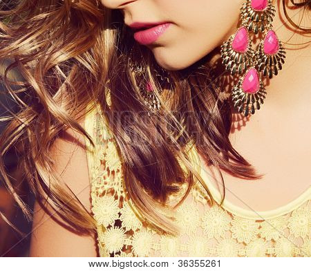 closeup of blond woman with long wet curly hair wearing pink lipstick and gold and pink neon earrings