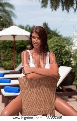 Beautiful Girl Model Relaxes In A Tropical Location In A Hotel Sitting On A Chair. Smile And Good Mo