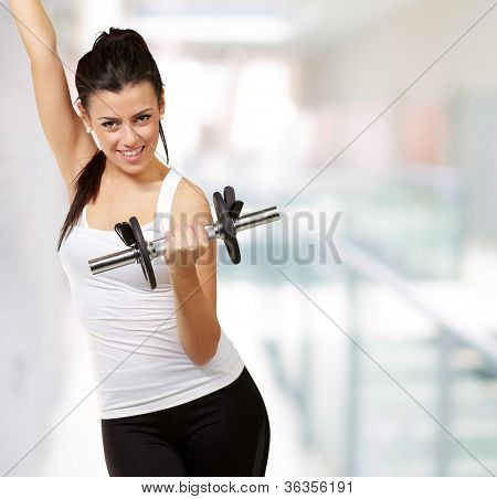 portrait of a young woman doing fitness with weights indoor