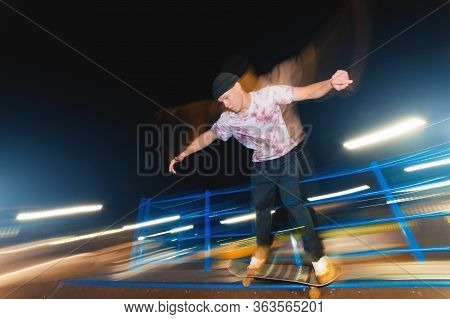 Stylish Young Skater In A Fashionably Tucked Hat Rides A Skatepark At Night. Night Photo With The Mo