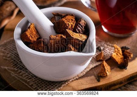 Chaga Mushroom Pieces In A Mortar And Pestle With Tea.