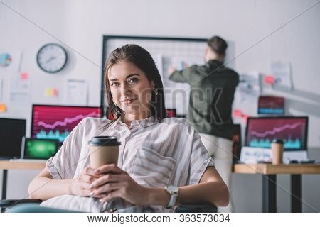 Smiling Data Analyst Holding Coffee To Go While Colleague Working In Office