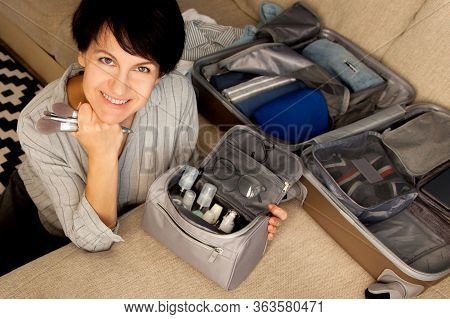 Open Grey Suitcase With Different Clothes And Cosmetics Packed For Journey At Home. Nordic Style Min