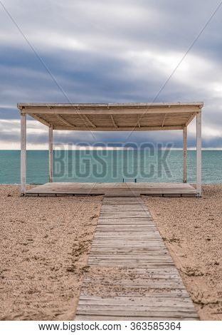 Wooden Walkway And Sunshades On Sand Beach With Azure Sea, Cloudy Sky Background. Empty Beach With S