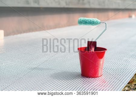 Paint Roller And A Bucket With Paint Next To A Building Exterior Wall. Painting House Plinth Outside
