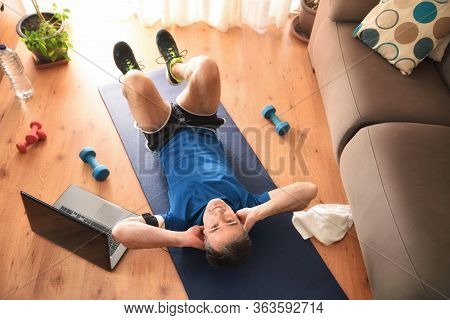 Man Doing Abdominal And Leg Exercises In The Living Room At Home Lying Down On A Mat Top View