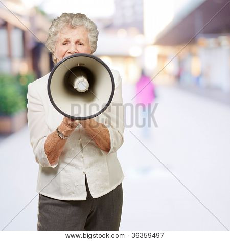 portrait of senior woman screaming with megaphone at city