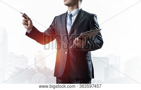 Businessman With Documents Pointing Away On White Background. Front View Of Standing Entrepreneur In