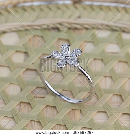 Cute Silver Ring In The Flower Shape Decorated With Diamond Display On Weaved Bamboo