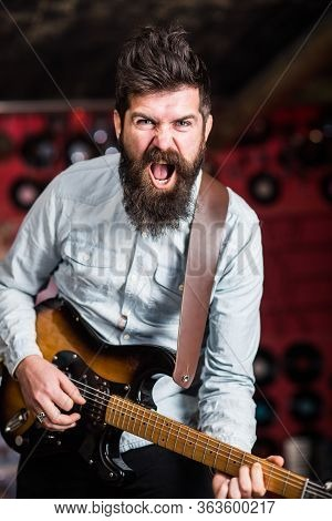 Rock Music Concept. Musician With Beard Play Electric Guitar. Talented Musician, Soloist, Singer Pla