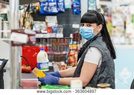 A Portrait Of Young Woman In A Medical Mask And Gloves, Working At The Checkout In A Supermarket. Co