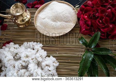 Items For The Indian Yajna Ritual. Garland Of White Flowers, Red Rose Petals And Copper Dish With Ri