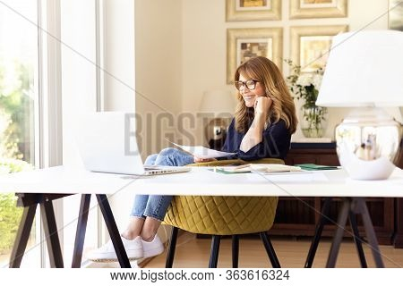 Shot Of Happy Smiling Businesswoman Using Her Laptop While Working At Home. Home Office.