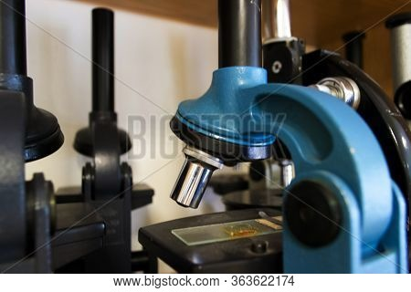 Close Up Blue Microscope Stands On Cabinet Shelf. Laboratory Equipment Kit. Science And Biology Conc