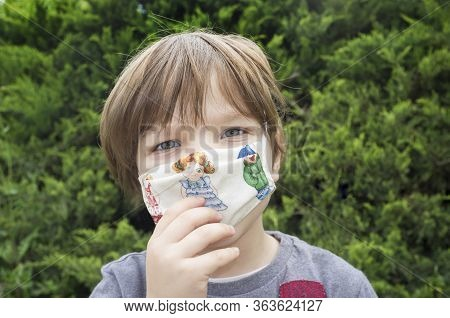 4 Years Little Boy Touching His Face Mask. He Bother Wearing The Mask
