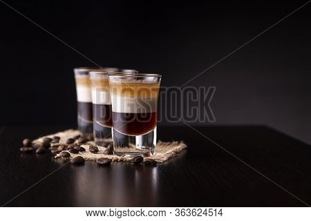 Three Shots Of B-52 Cocktail Placed On A Bar Counter With Copy Space; B 52 Cocktail Happy Hour