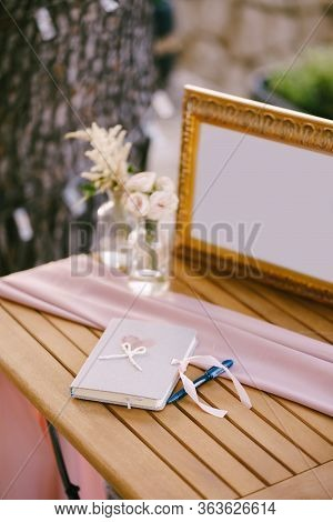 Wedding Wish Album. A Notebook For Wedding Wish Entries, A Blue Pen, Flowers In A Vase Of Water And
