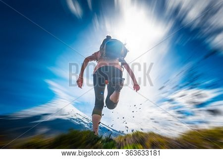 Young woman hiker runs on the trail with snow capped volcano of Osorno on the background and rocks flying in the air on the foreground. Chilean Patagonia