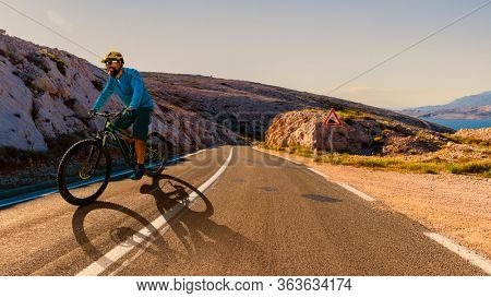 Man cycling on electric bike, rides mountain step road. Man riding on bike in Croatian landscape. Outdoor sport activity.