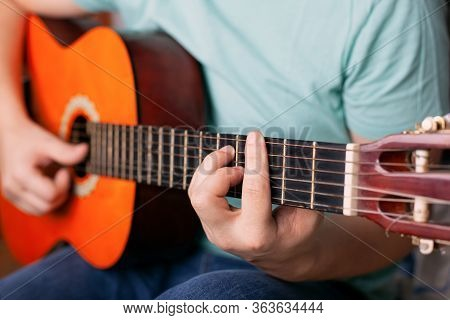 Guy Plays Acoustic Guitar, Man Finger Holding A Bar Chord. Learn To Play A Musical Instrument.