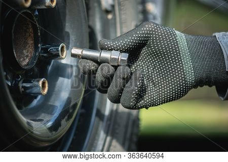 Tire Worker Removes Wheel From A Car Close Up.