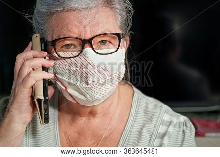 Elderly Senior Woman With Glasses Wearing Hand Made Cotton Mouth Nose Virus Face Mask, Talking Over
