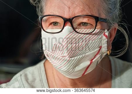 Elderly Senior Woman With Glasses Wearing Hand Made Cotton Mouth Nose Virus Face Mask. Coronavirus C