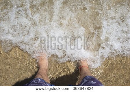 Top View Of Man's Feet (barefoot) On The Sand At The Surf Waves Over Them. Point Of View On Legs In