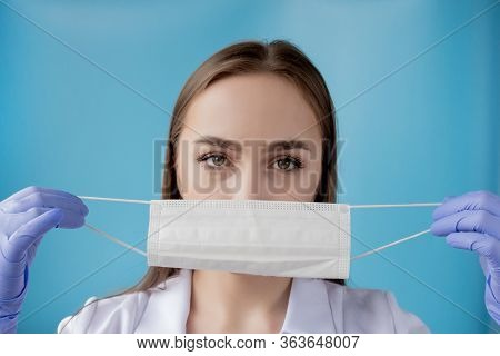 Doctor Nurse Smiling Behind Surgeon Mask. Closeup Portrait Of Young Caucasian Woman Model On Blue Ba