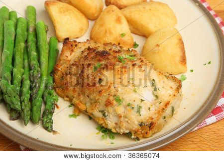 Chicken kiev, stuffed with garlic and herb butter, with asparagus and roast potatoes.