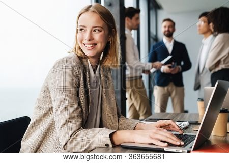 Attractive young smiling confident businesswoman sitting at the office table with group of colleagues in the background, working on laptop computer