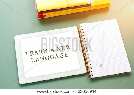 Flatlay On A Green Background Tablet With The Inscription Learn A New Language, Notebook, Pen And Te