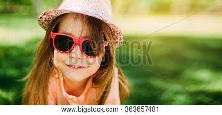 Portrait of a little cute girl wearing a hat and sunglasses outdoors. Copy space.