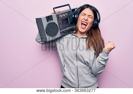 Young beautiful brunette woman listening to music using vintage boombox and headphones screaming proud, celebrating victory and success very excited with raised arm