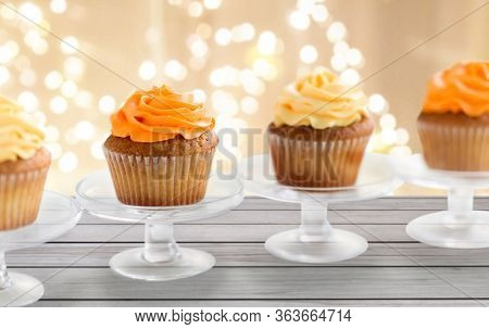 food, pastry and sweets concept - cupcakes with buttercream frosting on glass confectionery stand over festive lights background