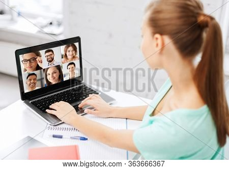 technology, remote job and online education concept - young woman or student girl with laptop computer having video call with colleagues or teachers at home