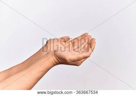 Hand of caucasian young man showing fingers over isolated white background asking and offering with both hands cupped, open palms doing assistance gesture