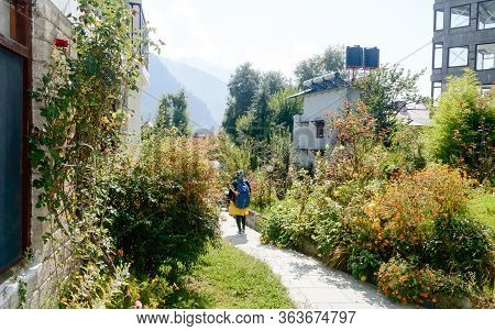 Rear View Solo Woman In Hiking Sportswear And With A Backpack On Her Shoulders. Sporty Woman With Ba