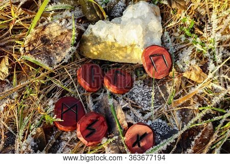 Carved Wood Runes And Quartz Druse On Hoarfrost Grass