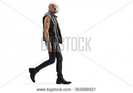 Full length profile shot of a punk man wearing a protective medical mask and walking isolated on white background