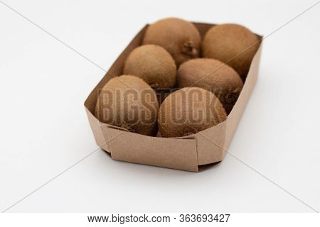 Carton Package Of Whole Brown Kiwi Fruits Closeup. Hairy Fresh Ripe Kiwifruits. Agriculture Or Organ