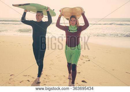 Couple With Surfboards Walking On Beach. Front View Of Middle Aged Man And Woman In Wetsuits Holding
