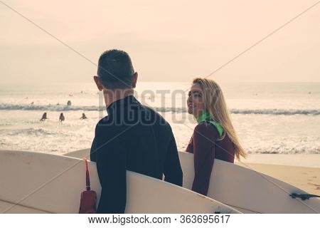 Couple Holding Surfboards And Walking On Beach. Cheerful Man And Woman In Wetsuits Holding Surfboard