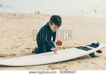 Child Waxing Surfboard On Beach. Cute Happy Little Boy In Wetsuit Kneeling On Sand And Waxing Surfbo